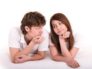 Молодая пара лежит на кровати и смотрит друг на друга